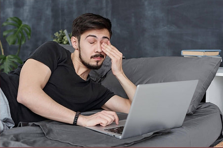 man falling asleep using laptop.adrenal burnout maybe